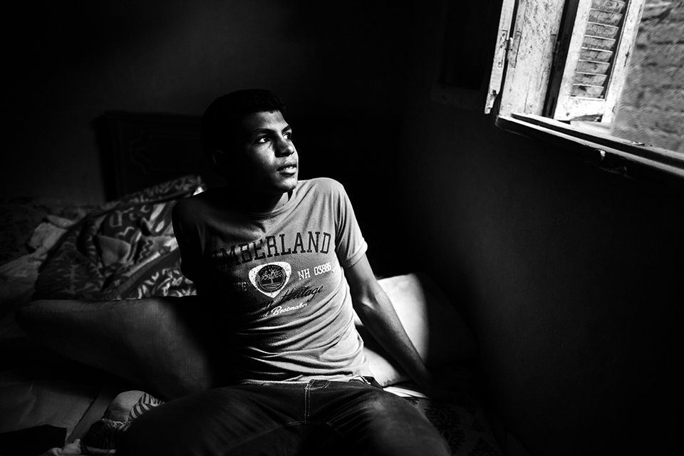 13 October 2014. Shobra Sandy: Mahmud Abdul, 17 years old, is pictured in the common bedroom that shares with the whole family in Shobra Sandy, a small village in an area where many young boys regularly attempt to scape to Europe by boats. Mahmud and his friend Mohamed (16) tried to flee together to Italy in December 2013, but the boat that departed from Alexandria sank near the Greek coast and was rescued by the Red Cross. They were repatriated later back home by the authorities. Mahmud is still dreaming to travel to Europe, but he is hesitant due to the scaring experience he suffered in that boat. For the time being, he will remain in the village, helping his family in the farm.Photo by Albert González Farran, IOM
